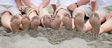 Family feet on beach in line. Feet each family member on the beach, in a line. Sand and seaweed under feet. Family dressed in white and shorts Stock Images