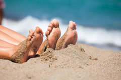 Family feet on a beach. Mother with daughter relaxing and sunbathing on a beach stock photo