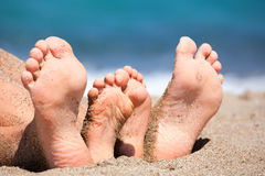Family feet on a beach. Mother with daughter relaxing and sunbathing on a beach royalty free stock image