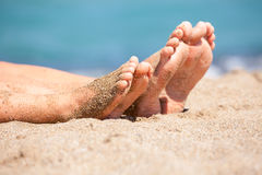 Family feet on a beach. Mother with daughter relaxing and sunbathing on a beach royalty free stock photo