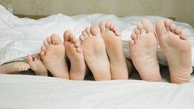 Family feet in bed under white blanket