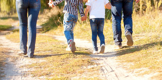 Family feet and legs. Rear view. Family feet and legs in jeans. Father, mother, son and daughter walking on the road. Rear view stock image
