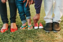 Family feet posing for baby announcement. Family feet and legs posing for baby announcement stock image