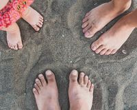 Family feet on the sand on the beach. Vacation concept stock image