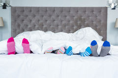 Family feet sticking out from the blanket. Family feet with socks sticking out from the blanket royalty free stock photos
