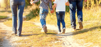 Family feet walking on the path. Rear view. Family feet and legs in jeans. Father, mother, son and daughter walking on the path. Rear view royalty free stock photography
