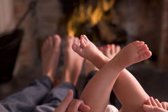 Family of feet warming at a fireplace Royalty Free Stock Image