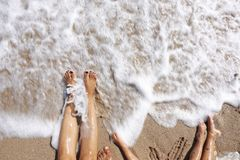 Family feet wet by the sea waves at the beach in summer holiday stock photos