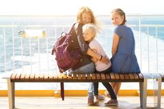Family on the ferry. Family - mother and two daughters sitting on a bench on the ferry and the sea in the background royalty free stock photos