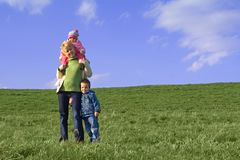 Family on the field in spring. Young woman and her children in the spring green field under the blue sky stock photography