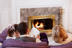 Family by the fire. Dad helps his daughter with reading while her mother watches Royalty Free Stock Images
