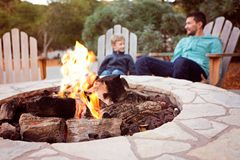 Family by firepit. View of firepit and happy smiling family of two, father and son, enjoying time together in the background Stock Image