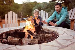 Family by firepit. View of firepit and happy smiling family of two, father and son, warming their hands by the fire and enjoying time together in the background Royalty Free Stock Photography
