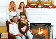 Family By Fireside. Portrait of a beautiful family by the fireplace, seasonally decorated with Autumn leaves Stock Image