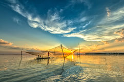 Family of fishermen repairing nets on the river Royalty Free Stock Photo