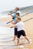 Family fishing on beach. Family fishing concept: grandpa took his grandsons fishing on beach, ready to cast the fishing line Stock Photo