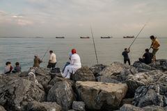 Family Fishing from the Rocks at Seaside. ISTANBUL, TURKEY - JUN 06, 2012: Family fishing from the rocks at seaside royalty free stock images