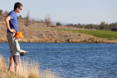 Family fishing. Young father teaching his cute son fishing royalty free stock photography