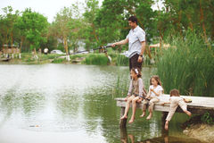 Family fishing. Young happy family with kids fishing in pond in summer Royalty Free Stock Photos