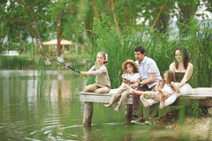 Family fishing. Young happy family with kids fishing in pond in summer Royalty Free Stock Images