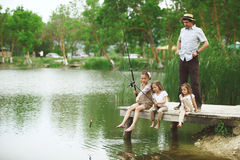 Family fishing. Young happy family with kids fishing in pond in summer Stock Images