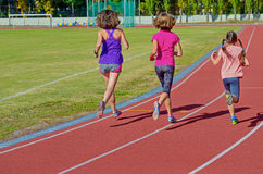 Family fitness, active mother and kids running on stadium track. Back view, training with children sport concept royalty free stock photography