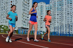 Family fitness, active mother and kids running on stadium track Royalty Free Stock Image