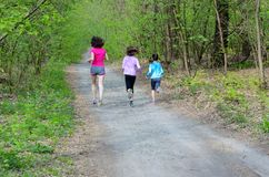 Family fitness and sport, active mother and kids jogging outdoors, running in forest. Family fitness and sport, happy active mother and kids jogging outdoors Royalty Free Stock Photography