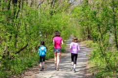Family fitness and sport, active mother and kids jogging outdoors, running in forest. Family fitness and sport, happy active mother and kids jogging outdoors royalty free stock image