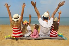 Family of five on the beach. Hands up. Travel and family vacation concept stock photo