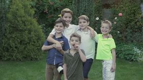 Family of five happy brothers. Portrait of adorable children outdoors in the garden. The brothers are hugging. The youngest boy eats a cucumber. Happy boys stock video