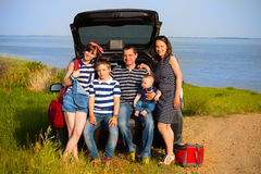 Family of five having fun on the beach going on summer vacation. Car travel and summer vacation concept Royalty Free Stock Images
