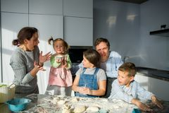 A family of five in the kitchen. Parents and children are cooking something. Useful and fun pastime Royalty Free Stock Image