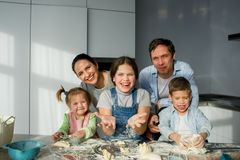 A family of five in the kitchen. Parents and children are cooking something. Useful and fun pastime Stock Photo