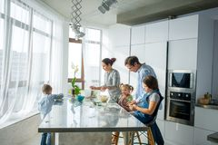 A family of five in the kitchen. Parents and children are cooking something. Useful and fun pastime Royalty Free Stock Photo