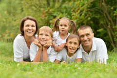 Family of five lying. On grass in summer park Stock Images