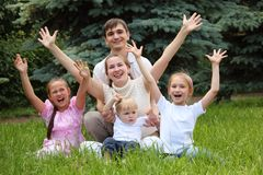 Family of five rejoice outdoor. In summer sit on grass, hands up royalty free stock image