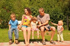 Family of five sit on bench. The family of five sit on bench stock photography