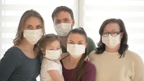 Family of five wears a protective medical mask to prevent coronavirus. Adults and children in medical masks to prevent