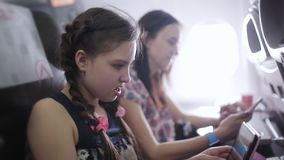 Family flies on vacation on a plane time passes through magazines and smartphones. Family will fly in and use the tablet stock video