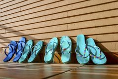 A family of flip flops rests and dries in the sun after a day on. The beach Royalty Free Stock Image