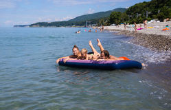 Family floating on an air mattress in the sea Stock Image