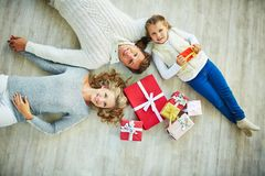 Family on the floor. Happy family with giftboxes lying on the floor and looking at camera Royalty Free Stock Photos