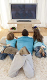 Family on floor in living-room watching television Royalty Free Stock Photography