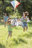 Family Flying Kite On Camping Holiday In Countryside stock photos