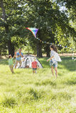 Family Flying Kite On Camping Holiday In Countryside Royalty Free Stock Images