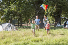 Family Flying Kite On Camping Holiday In Countryside Royalty Free Stock Photo