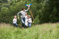 Family Flying Kite In Countryside. Running Towards Camera Royalty Free Stock Image