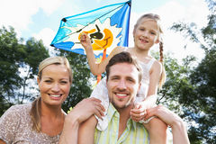 Family Flying Kite In Countryside. Smiling To Camera Royalty Free Stock Image