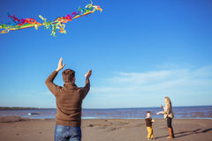 The family is flying a kite at the seashore Stock Images